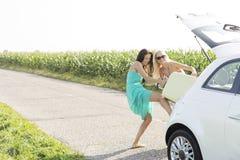 Amis féminins heureux poussant le bagage dans le tronc de voiture contre le ciel clair Photographie stock libre de droits
