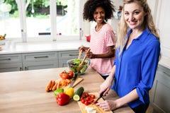 Amis féminins heureux préparant la nourriture à la maison Photo stock