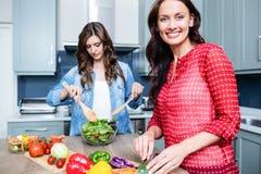 Amis féminins heureux préparant la salade végétale Photos libres de droits