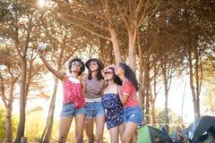Amis féminins heureux prenant le selfie au terrain de camping Photos stock