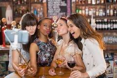 Amis féminins heureux prenant le selfie dans le bar Images stock