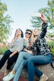 Amis féminins heureux prenant le selfie sur la rue Images libres de droits