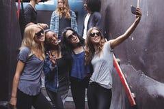 Amis féminins heureux prenant le selfie tout en se tenant sur des étapes Photographie stock