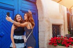 Amis féminins heureux prenant le selfie utilisant le smartphone marchant sur de vieilles rues de ville Photo stock