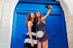 Amis féminins heureux prenant le selfie utilisant le smartphone marchant sur de vieilles rues de ville Image stock