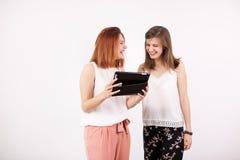 Amis féminins heureux regardant une tablette Photo stock