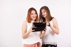 Amis féminins heureux regardant une tablette Photo libre de droits