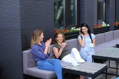 Amis féminins heureux riant du café et du bavardage, café potable Photographie stock