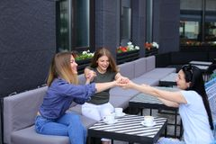 Amis féminins heureux s'asseyant au café et tenant des mains Image libre de droits