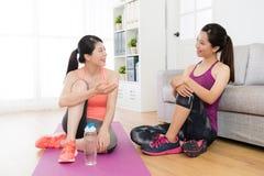 Amis féminins heureux s'asseyant sur le plancher de salon Image libre de droits