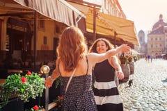 Amis féminins heureux se réunissant sur la vieille rue de ville en été Vraies émotions des meilleures amies de femmes Photos stock