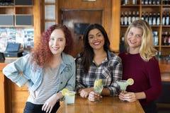 Amis féminins heureux se tenant ensemble dans la barre Photographie stock