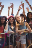 Amis féminins heureux se tenant prêt la balustrade au festival de musique Photographie stock libre de droits
