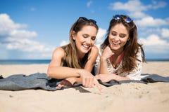 Amis féminins heureux se trouvant sur la plage regardant le sable Image libre de droits