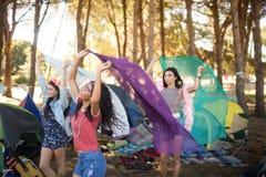 Amis féminins heureux tenant des écharpes au terrain de camping Image libre de droits