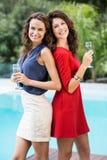 Amis féminins heureux tenant des cannelures de champagne Photo stock
