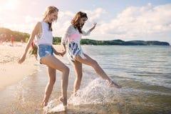 Amis féminins heureux tenant des mains éclaboussant l'eau Photo stock