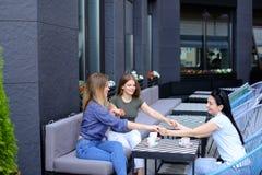 Amis féminins heureux tenant des mains au café et buvant du café Photo libre de droits