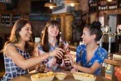 Amis féminins heureux tenant griller des bouteilles à bière Photo libre de droits