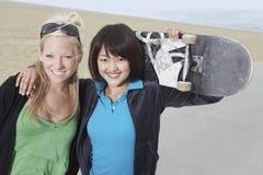 Amis féminins heureux tenant la planche à roulettes Photographie stock libre de droits