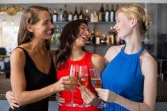 Amis féminins heureux tenant le verre de la cannelure de champagne Photos stock