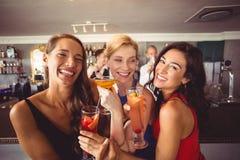 Amis féminins heureux tenant le verre du cocktail Photos libres de droits
