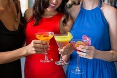 Amis féminins heureux tenant le verre du cocktail Image stock