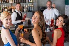 Amis féminins heureux tenant le verre du cocktail au compteur de barre Photos libres de droits