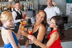 Amis féminins heureux tenant le verre du cocktail au compteur de barre Images libres de droits