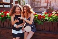 Amis féminins heureux vérifiant le réseau social utilisant le téléphone par le café sur la rue de ville Fille se dirigeant au sma Image stock