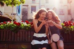 Amis féminins heureux vérifiant le réseau social utilisant le téléphone par le café sur la rue de ville jeunes de femme d'été de  Photos libres de droits