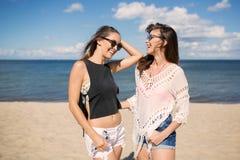 Amis féminins insouciants riant ensemble sur la plage Images stock