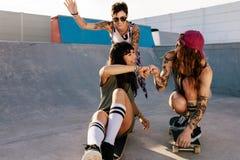 Amis féminins jouant avec la planche à roulettes au parc de patin Photos libres de droits
