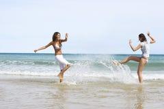 Amis féminins jouant dans l'eau à la plage Photos libres de droits