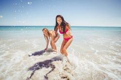 Amis féminins jouant sur la plage Image stock