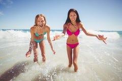 Amis féminins jouant sur la plage Images stock