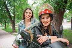 Amis féminins joyeux appréciant le voyage sur le vélo Images libres de droits