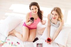 Amis féminins joyeux ayant l'amusement à la maison Image libre de droits
