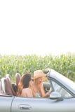 Amis féminins lisant la carte dans le convertible contre le ciel clair Photos libres de droits