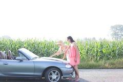 Amis féminins lisant la carte sur le convertible contre le ciel clair Images libres de droits