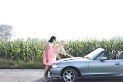 Amis féminins lisant la carte sur le convertible contre le ciel clair Photographie stock