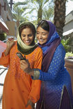 Amis féminins lisant le message textuel Photos stock