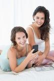 Amis féminins lisant le message textuel dans le lit Photographie stock