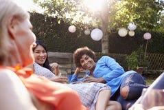 Amis féminins mûrs appréciant des boissons dans l'arrière-cour ensemble Image libre de droits
