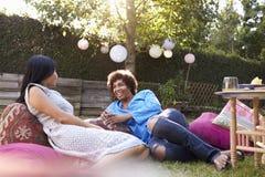Amis féminins mûrs appréciant des boissons dans l'arrière-cour ensemble Photographie stock libre de droits