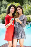 Amis féminins magnifiques par la piscine Photos stock