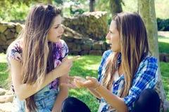 Amis féminins malheureux discutant en parc Photo libre de droits
