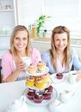 Amis féminins mangeant des pâtisseries et buvant du café Photographie stock libre de droits