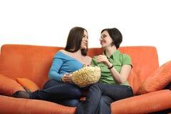 Amis féminins mangeant du maïs éclaté et regardant la TV à la maison Image libre de droits