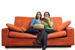 Amis féminins mangeant du maïs éclaté et regardant la TV à la maison Images stock